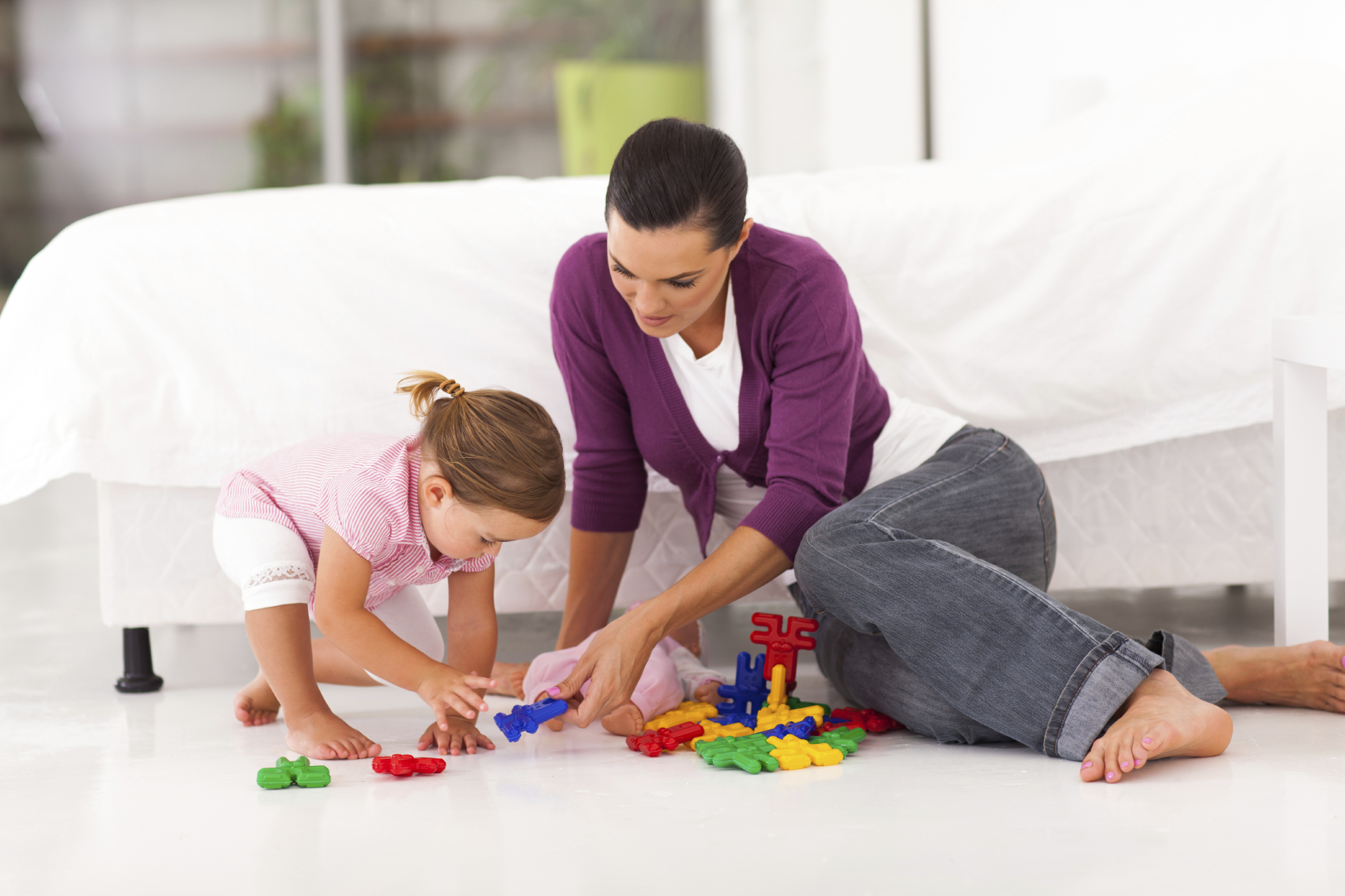 happy mother and daughter playing with toy on bedroom floor